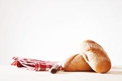 Två wholemealbullar med en handduk och en gammal brödkniv Royaltyfri Foto