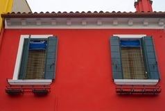 Två Windows med gröna slutare på den röda väggen, Burano, Italien royaltyfria bilder