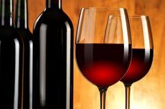 Två wineglasses och flaskor av rött vin Royaltyfria Bilder