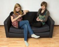 Två yong kvinnor med mobiltelefoner royaltyfri fotografi
