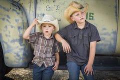 Två Young Boys som bär cowboyHats Leaning Against den antika lastbilen fotografering för bildbyråer