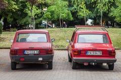 Två Zastava och Yugo 55 parkerade röda bilar Också bekant som Skala, är det en släktnamn för en familj av bilar som byggs av Zast Royaltyfri Bild