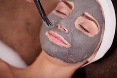 Tvål-, handduk- och blommasnowdrops Ung kvinna med den närande ansikts- maskeringen i skönhetsalong, slut upp Arkivfoto