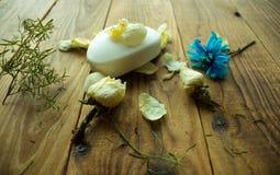 Tvål och blommor på en träbakgrund royaltyfri foto