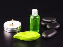 Tvål, stearinljus, flaska av olja och brunnsortstenar på den svarta tabellen Fotografering för Bildbyråer
