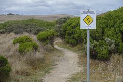 Tvåspråkig varningsvägvisare som är på engelska, och kines av giftormaktivitet på en vandringsled nära den stora havvägen av Aust royaltyfria foton