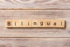 Tvåspråkigt ord som är skriftligt på träsnittet tvåspråkig text på tabellen, begrepp arkivbild