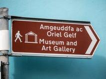 Tvåspråkigt tecken som ger riktningar till museet och konstgallerit royaltyfri bild