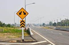 Tvåvägsföreningspunkt- och trafikö som varnar framåt tecknet Fotografering för Bildbyråer