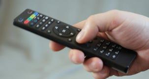 Κλείστε επάνω επανδρώνει τον τηλεχειρισμό TV εκμετάλλευσης χεριών και τα μεταβαλλόμενα τηλεοπτικά κανάλια φιλμ μικρού μήκους