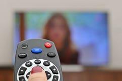 TV προσοχής και χρησιμοποίηση του μακρινού ελεγκτή Στοκ εικόνα με δικαίωμα ελεύθερης χρήσης