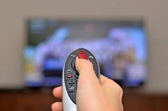 TV προσοχής και χρησιμοποίηση του μακρινού ελεγκτή Στοκ Εικόνες