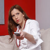 TV. Woman holding a remote control Stock Photos