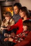 TV προσοχής οικογενειακής χαλάρωσης από την άνετη πυρκαγιά κούτσουρων Στοκ Φωτογραφία