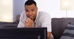 Αφρικανικό άτομο που προσέχει το παιχνίδι στη TV Στοκ φωτογραφίες με δικαίωμα ελεύθερης χρήσης