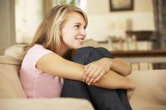 Συνεδρίαση έφηβη χαμόγελου στον καναπέ που προσέχει στο σπίτι τη TV Στοκ Εικόνα