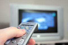 TV. Thumb on remote control in front of television Stock Photography