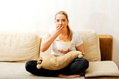Νέα γυναίκα που προσέχει τη TV και που τρώει τα τσιπ Στοκ Εικόνες