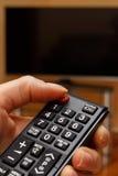 Χέρι που κρατά τον τηλεχειρισμό για την τηλεόραση, που επιλέγει το κανάλι στη TV Στοκ εικόνες με δικαίωμα ελεύθερης χρήσης