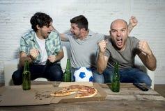 Φανατικοί οπαδοί ποδοσφαίρου φίλων που προσέχουν παιχνίδι στο στόχο εορτασμού TV που κραυγάζει τρελλό ευτυχή Στοκ Φωτογραφία