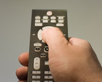 Tv. Photo of hand with remote, man sitting on the coach watching TV Royalty Free Stock Photos