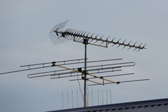 A tv aerial on a tiled roof top isolated against a clear blue sky royalty free stock images