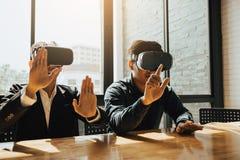 Tv? aff?rsaff?rspersoner med virtuell verkligheth?rlurar med mikrofon i kontoret royaltyfri bild