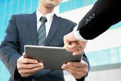 Två affärsmän som ser minnestavladatoren med en hand som pekar skärmen Arkivfoton