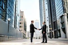 Två affärsmän som skakar händer på företags byggnader för bakgrundskontor Arkivbild
