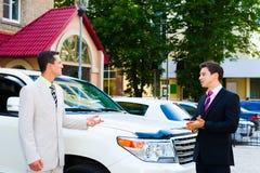 Två affärsmän som talar om bilar Arkivfoto
