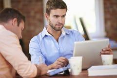 Två affärsmän som tillsammans arbetar på skrivbordet Arkivfoto