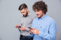 Två allvarliga män som använder smartphonen Arkivfoto