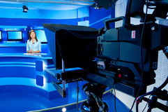 TV anchorwoman at TV studio. Television woman announcer at studio during live broadcasting Stock Photography