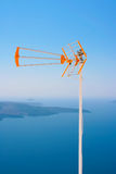 TV antenna against volcano in Santorini Royalty Free Stock Photo
