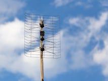 TV antenna on a background of blue sky Stock Photos