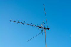 TV antenna on blue sky background. TV antenna for receiving terrestrial television UHF band against the blue sky Royalty Free Stock Photos