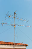 TV antenna on red roof Stock Photography