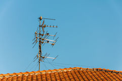 TV antenna on red roof Stock Photo