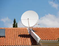 Tv antenna on the red tile roof Stock Photography