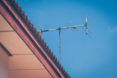 TV antenna on roof of house with blue sky background. royalty free stock image