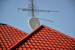TV antennas and satellite dish for television mounted on the tiled roof of house isolated on blue sky background in countryside Royalty Free Stock Images