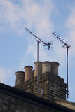 TV arial antenna chimney roof building sunset Royalty Free Stock Images