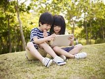 Två asiatiska barn som utomhus använder minnestavlan Arkivbild