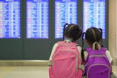 Tv? asiatiska barnflickor med ryggs?cken som kontrollerar deras flyg p? informationsbr?det i terminal f?r internationell flygplat royaltyfri fotografi