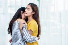 Tv? asiatiska lesbiska kvinnor som tillsammans ser i sovrum Parfolk och sk?nhetbegrepp Lyckliga livsstilar och hem- s?tt hem- tem royaltyfri bild