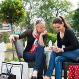 Två attraktiva unga kvinnliga vänner som tycker om en dag ut efter lyckad shopping Arkivbild