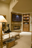 TV au-dessus de cheminée avec la chaise étendue dans le premier plan Photographie stock