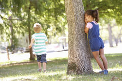 Två barn som spelar kurragömma parkerar in Arkivfoton