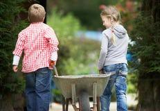 Två barn som spelar med skottkärran i trädgård Royaltyfria Foton