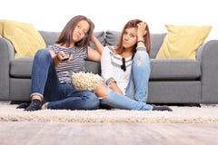 Två borrade tonårs- flickor som håller ögonen på TV Fotografering för Bildbyråer